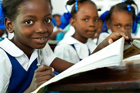 Smiling African girls sitting at desks with books and pencils